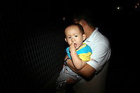 CHINA. Beijing. A young child being held by his father. 2008.