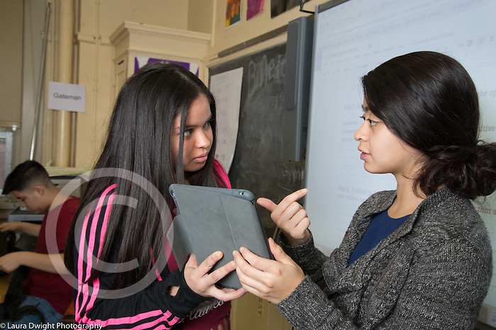High School Classrooms female teacher talking to female student about her work, holding laptop computer