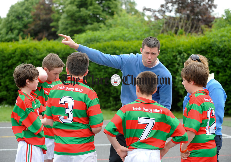 Teacher Fergal Lynch talks with his Quin NS charges before playing in the final at the Marian Keane Basketball finals at Scoil na Mainstreach, Quin. Photograph by John Kelly.