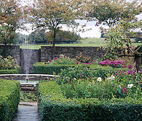 Formal flower beds surround a circular fountain in the walled garden