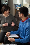 15 year old teenage boy at home with mother, talking to her about high school academic decisions