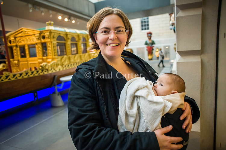 Portrait of a mother breastfeeding her baby from a sling in a museum.<br /> <br /> London, England, UK<br /> 08/03/2015<br /> <br /> © Paul Carter / wdiip.co.uk