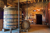 In the winery: an old oak vat an old oak barrel and stone walls. Very old fashioned winery and wine cellar in Burgundy, Bourgogne. Burgundy Cote d'Or France Europe