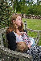 A mother  breastfeeding her child during a family outing to a local park and gardens.<br /> <br /> 11-06-2015<br /> Hampshire, England, UK<br /> <br /> © Paul Carter / wdiip.co.uk