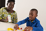 Seven year old boy at home, doing math assignment for homework, assisted by mother, usng cube counters and flash cards