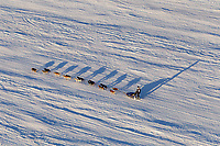 Kris Denure runs on the Yentna river with long shadows cast on the snow a few hours after leaving the re-start line in Willow during the 2011 Iditarod.