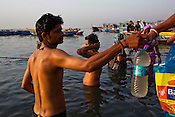 A young man fills up a bottle of Ganges water for a woman on the ghats in the ancient city of Varanasi in Uttar Pradesh, India. Photograph: Sanjit Das/Panos