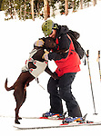 Crested Butte ski patrolman Shawn Williams and his chocolate avalanche rescue lab, Ziggy near the summit of the Colorado ski mountain.