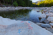 Graffiti on rocks along the East Branch of the Pemigewasset River, near Lincoln Woods Trail, in the New Hampshire White Mountains in August 2020. Because of the Coronavirus Pandemic, the White Mountains have seen a surge in use, and along with this comes more human impact.
