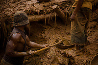 """Congolese miner Bevins in a blue shirt and hat digs in the bottom of a pit mine. """" It was only fate that brought us here  6 weeks ago. Others have  dug here before. There is no reason why we chose theis place. We are lucky here, the work is hard, but we have found  good gold and  the price is higher  here now."""".Artisanal  Miners sift through the  tailings in the shadow of  an abandoned processing  plant in Kanga, outside Mongbwalu, north-eastern DRC..The tailings are bits of stone and silt left over from the refinery process. This processing plant was  the central refinery for gold found in Ituri province. Even during  the war it was pushing out 10-20 kilos of gold per month. .The shell of the buildings and the waste left behind are all that remain the company fled during the war. Since being abandoned in 2001 anything that could be carried away and used elsewhere or sold as scrap has disappeared.."""