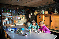 Two women hikers reading a book and relaxing inside the Capanna Nimi while hiking the Via Alta Via Maggia, a difficult week long trek from Locarno to Broglio, Switzerland