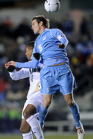 North Carolina Tar Heals Zach Loyd (5) battles for a header with Akron Zips Teal Bunbury (12) during the second semi-final match of the 2009 NCAA Men's College Cup at WakeMed Soccer Park in Cary, NC on December 11, 2009.