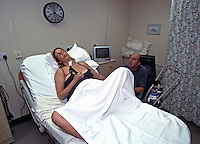 Expecting mother in delivery room using entonox gas to help relieve the pain caused by the contractions as she starts to enter into labour. Her husband is with her holding her hand. This image may only be used to portray the subject in a positive manner..©shoutpictures.com..john@shoutpictures.com