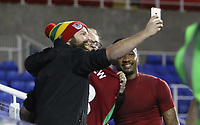 Jordan Ayew of Swansea City stands with fans after giving away his shirt after the final whistle of the Carabao Cup Third Round match between Reading and Swansea City at Madejski Stadium, Reading, England, UK. Tuesday 19 September 2017