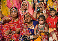 Rajasthani women  and girls dress in their finest clothing and jewelry to celebrate at the GANGUR FESTIVAL also know as the MEWAR FESTIVAL - UDAIPUR, RAJASTHAN, INDIA