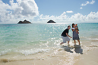 A family of three enjoying each other at Lanikai Beach, O'ahu, with the Mokulua Islands in the distance.