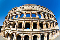 Fisheye perspective on the iconic Ancient Roman Colosseum (Flavian Amphitheatre) under a blue sky, in Rome Italy, Southern Europe