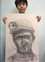 BNPS.co.uk (01202 558833)<br /> Pic: SimoneGreenfield/BNPS<br /> <br /> Video download link: https://we.tl/t-bJLf5479nt<br /> <br /> Pictured: 'Coal Miner' and Lucas.<br /> <br /> A nine-year-old artist described as an 'outstanding' talent will have his work exhibited by the Royal Academy.<br /> <br /> Lucas Greenfield began drawing life-like portraits of his favourite footballers during the first lockdown.<br /> <br /> His parents were amazed by the sudden out-pour of work which followed, including pictures of pets commissioned and paid for by his teachers.