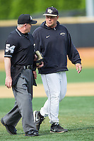 Wake Forest Demon Deacons assistant coach Dennis Healy (31) chats with home plate umpire Danny Collins as he walks back to the dugout during the game against the Virginia Cavaliers at Wake Forest Baseball Park on May 17, 2014 in Winston-Salem, North Carolina.  The Demon Deacons defeated the Cavaliers 4-3.  (Brian Westerholt/Four Seam Images)