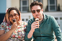 A couple enjoy a break with a walk and an ice cream on the Aberystwyth promanade. Sunshine and warm weather in Aberystwyth, west Wales, UK. Friday 13 May 2016