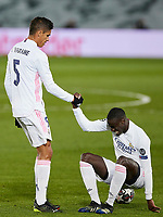 16th March 2021; Madrid, Spain;  Raphael Varane of Real Madrid helps his teammate Ferland Mendy during the Champions League match, round of 16, between Real Madrid and Atalanta played at Alfredo Di Stefano Stadium