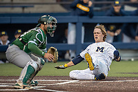 Michigan Wolverines outfielder Jesse Franklin (7) slides safely home in front of catcher Nick Jones during the NCAA baseball game against the Eastern Michigan Eagles on May 8, 2019 at Ray Fisher Stadium in Ann Arbor, Michigan. Michigan defeated Eastern Michigan 10-1. (Andrew Woolley/Four Seam Images)