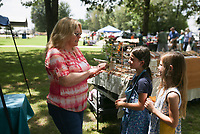 Melinda Anderson (from left) shows her jewelry to Violet Ahern, 8 and Hazel Ahern, 6, at her booth Luvmea Jewlry, Saturday, July 24, 2021 during a farmer's market at Harry Sbanotto Park in Tontitown. The Towntitown Farmer's Market hosted an antique car show and customs exhibit in addition to their regular farmer's market. Check out nwaonline.com/210725Daily/ for today's photo gallery. <br /> (NWA Democrat-Gazette/Charlie Kaijo)