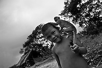 A Nukak boy plays with a baby monkey during the rain in a refugee camp close to San Jose del Guaviare, Colombia, 4 September 2009. The Nukak Maku people, nomadic hunter-gatherers from Amazonia, were violently driven out of the jungle by the Colombian guerilla and paramilitary squads. Now, roughly cut off their original tribal lifestyle, they stuck between worlds. They learn from the (mainly Christian) aid workers to use clothes, to listen to the radio, to beg for money. Although their digestion suffer, they love to eat sweets, cookies and other western food. They have hunted out all the animals around and now there is nothing left for them. Nukak can not return to the jungle, their world has already passed through an irreversible change.