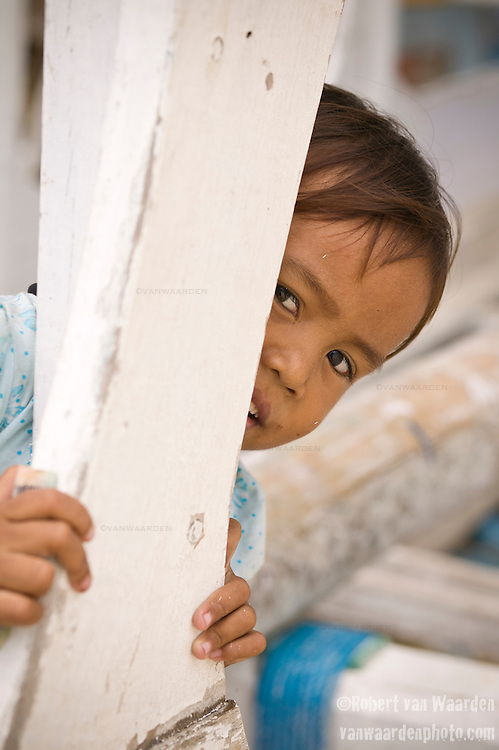 A young girl peers around a fishing boat for the camera on Gili Trawangan, Lombok, Indonesia.