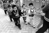 School children being tied up on the way to school, to avoid being stolen in Guangzhou, China. Kidnapping of young children especially boys are in the thousands as parents without a son are willing to pay large ammounts for a son.<br />