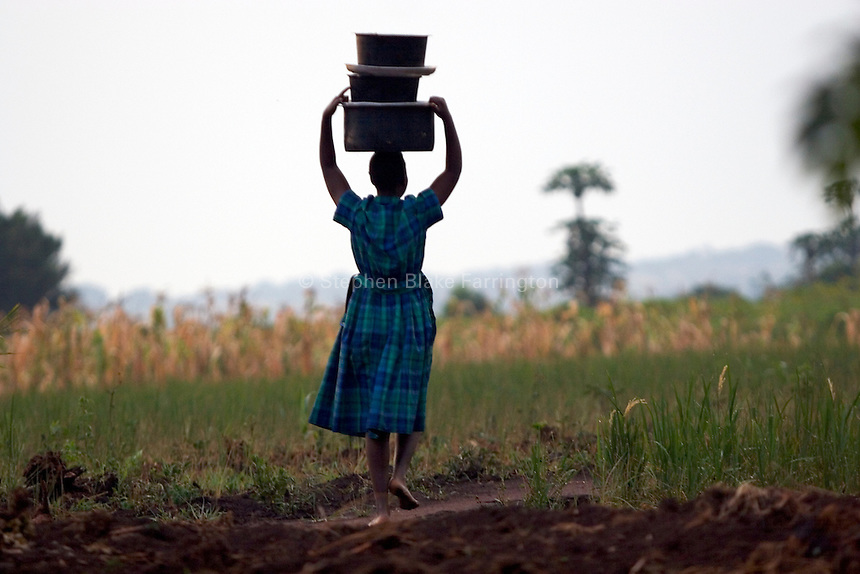 Empowering Victims of War- Early in the morning this young girl begins her daily tasks. Canaan Family Farm lends land to displaced people from the Northern conflict to have them learn the benefits of work and empowerment. Rwakayata, Masindi, Uganda, Africa. December 2005 © Stephen Blake Farrington