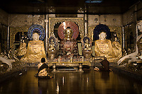 A worshipper and monk pray inside the Shwedagon Pagoda.