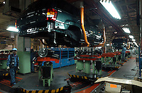 "Workers assemble parts of a ""Grand Cherokee"" of Chrysler in the Beijing Jeep factory.."