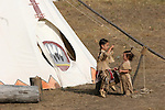 A young Native American Indian boy putting on a bone necklace on a young girl next to their tipi or home