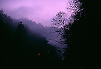 Truck Lights dot the side of the mountain as sun rises onto a foggy landscape in at a mountaintop removal mine site.