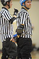 Referees wait in the centre zone during the Roller Derby match between the Richter City All Stars and the Victoria Roller Derby Queen Bees at TSB Bank Arena, Wellington, New Zealand on Saturday, 13 July 2013. Photo: Dave Lintott / lintottphoto.co.nz