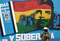 La Paz, Bolivia<br /> A picture dated December 6, 2005 shows a bolivian lady walking infront of a wall with the image of Che Guevara and leftist Movement Towards Socialism  (MAS) leader Evo Morales, an Aymara native and coca defender, less than two weeks before the presidential elections.