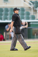 Home plate umpire Skyler Shown walks out to the mound during the game between the Delmarva Shorebirds and the Kannapolis Intimidators at CMC-NorthEast Stadium on July 1, 2014 in Kannapolis, North Carolina.  The Intimidators defeated the Shorebirds 5-2. (Brian Westerholt/Four Seam Images)