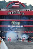 Jun. 18, 2011; Bristol, TN, USA: NHRA funny car driver Cruz Pedregon (left) does a burnout alongside Bob Tasca III during qualifying for the Thunder Valley Nationals at Bristol Dragway. Mandatory Credit: Mark J. Rebilas-