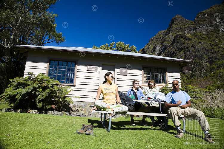 Hikers resting in front of cabin in Maui's Haleakala National Park