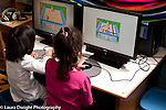 Preschool 3-4 year olds two girls using computers side by side, using same program