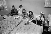 Part of a Bangladeshi family of five children and two adults in an unfit two bedroom flat in Levita House, Kings Cross, London 1990.