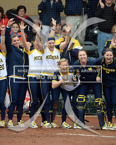 Michigan Wolverines players including utility player Kelsey Susalla (7) and outfielder Brandi Virgil (2) wait for shortstop Sierra Romero (32 - not shown) after hitting a grand slam home run during the season opener against the Florida Gators on February 8, 2014 at the USF Softball Stadium in Tampa, Florida.  Florida defeated Michigan 9-4 in extra innings.  (Copyright Mike Janes Photography)