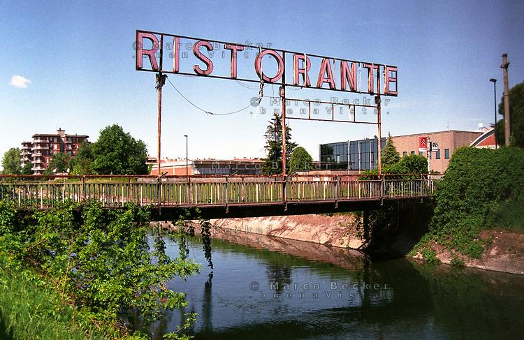 Limbiate (Monza e Brianza). Una vecchia, grande insegna luminosa di un ristorante su un ponte del canale Villoresi --- Limbiate (Monza e Brianza). An old, big lighted sign of a restaurant on a bridge over the canal Villoresi