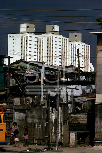 Sao Paulo, Brazil. Shanty town (favela) shacks with modern high-rise apartment buildings behind.