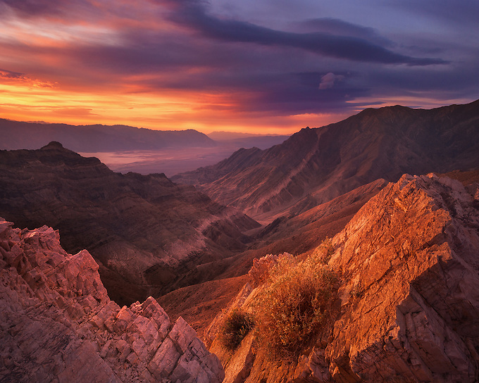 Warm reflected light from the sunrise gives a soft glow to the rocks and valley below.