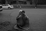 An Afghan mother holdins her infant child waits along a thoroughfare in Kabul on October 30, 2008.