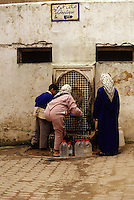 Fez, Morocco - Women Get Water at Public Fountain in the Old City of Fez.  Many homes do not have running water.  Sign on the wall above the fountain points to a public pay telephone.