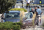 Officials investigate a shooting at an IHOP restaurant in Carson City, Nev., on Tuesday, Sept. 6, 2011. Four people died, including the gunman, and six more were injured. Investigators said after leaving the restaurant, the suspect drove in circles in the parking lot shooting from his car, seen here with mutltiple bullet holes. (AP Photo/Cathleen Allison)