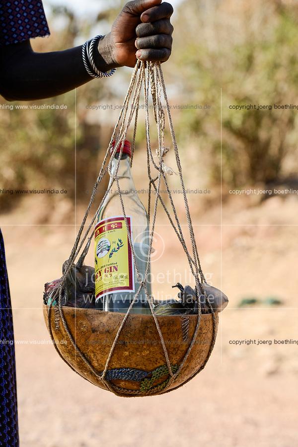 ETHIOPIA Province Benishangul-Gumuz, town Debate, Gumuz women carrying goods with yoke from the market to their village, bottle of gin / AETHIOPIEN, Provinz Benishangul-Gumuz, Stadt Debate, Gumuz Frauen mit Tragjoch gehen zum Markt